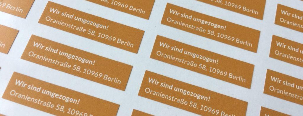 Auf dem Bild sind Sticker mit der neuen Adresse der BAG RelEx zu sehen: Oranienstraße 58, 10969 Berlin